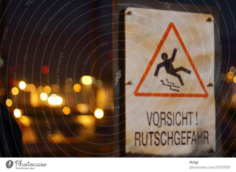 """Warnschild """"Vorsicht Rutschgefahr"""" mit leuchtendem Bokeh vor dunklem Hintergrund Stadt Kunststoff Zeichen Schriftzeichen Hinweisschild festhalten Kommunizieren"""