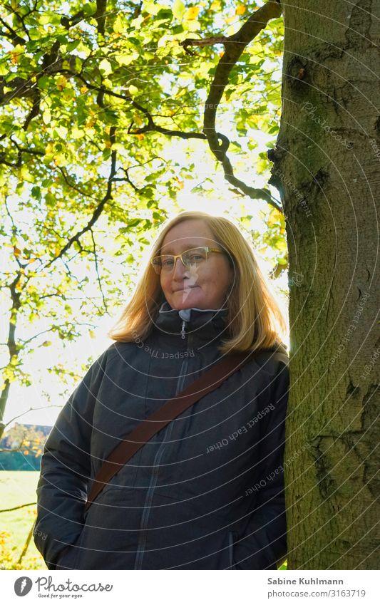 Innehalten Mensch feminin Frau Erwachsene 1 45-60 Jahre Natur Sonnenlicht Herbst Schönes Wetter Baum Wald Jacke blond Scheitel Erholung Lächeln stehen einfach