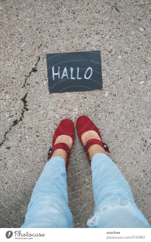"""frau steht vor einer kleinen tafel mit dem wort """"hallo"""" darauf geschrieben .. Frau weiblich Beine Füße Schuhe Jeans stehen Straße Asphalt Tafel Geschriebenes"""
