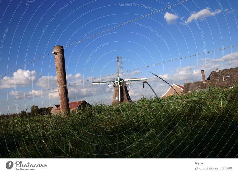 windmühle Himmel grün blau Wolken Wiese Gras Holz Perspektive Zaun Draht Pfosten zentral elektronisch Windmühle