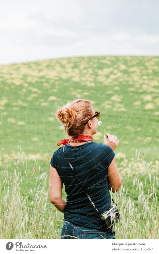 Junge Frau riecht Blume auf dem Feld Lifestyle Freude Ferien & Urlaub & Reisen Tourismus Abenteuer Freiheit Sommerurlaub Fotokamera Mensch feminin Jugendliche