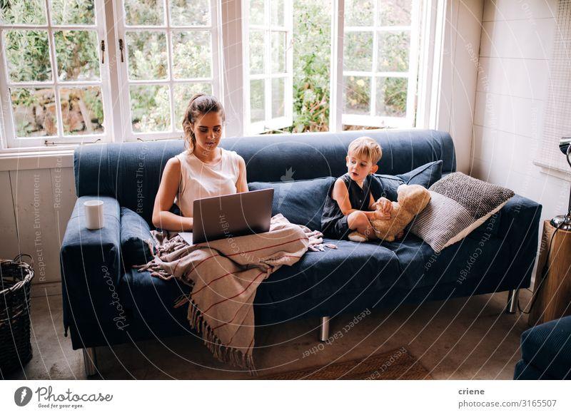 Mutter arbeitet am Laptop neben ihrem Sohn. Lifestyle Glück Erholung Freizeit & Hobby lesen Sofa Kind Arbeit & Erwerbstätigkeit Business Computer Notebook
