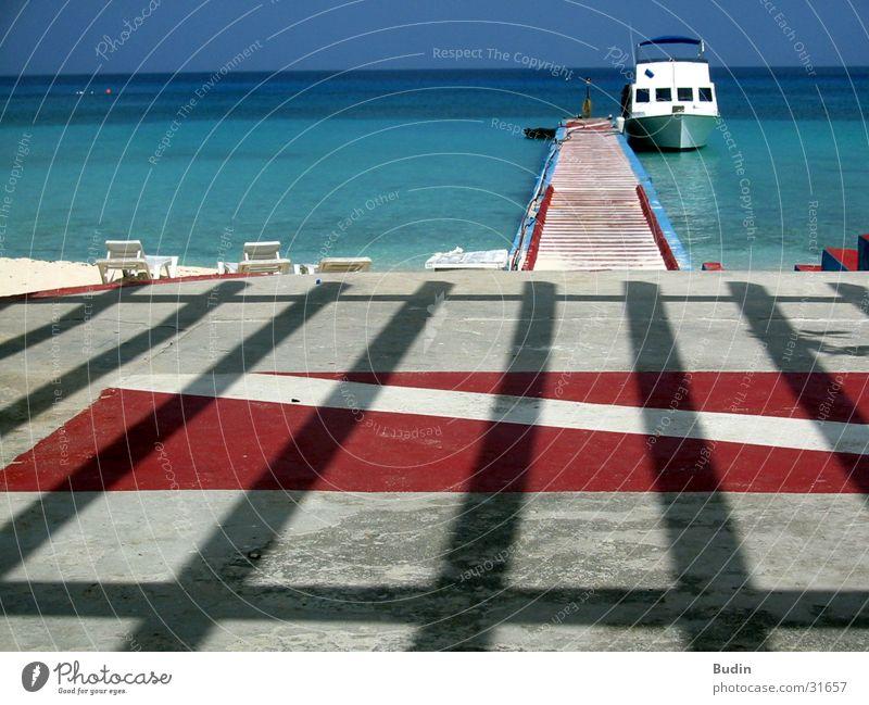 el barco Steg Wasserfahrzeug Strand Meer rot Streifen Horizont Ankunft Ferien & Urlaub & Reisen türkis Kuba Schatten Balken Ausflug