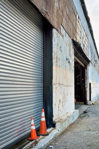 Zwei bunte Vögel schleichen sich an alt blau Stadt Haus Wand Gebäude Mauer orange Fassade paarweise Verkehr Perspektive USA warten Vergangenheit Bauwerk