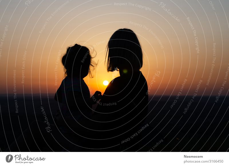 Mutter und Tochter, die sitzen und den Sonnenuntergang betrachten. Freude schön Ferien & Urlaub & Reisen Freiheit Sommer Meer Kind Baby Kleinkind Frau