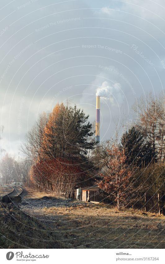 Herbstliche Stadtrandimpression mit rauchendem Schornstein herbstlich Sträucher Baum Wiese Gleise Rauch Heizkraftwerk bedeckter Himmel Herbstimpression