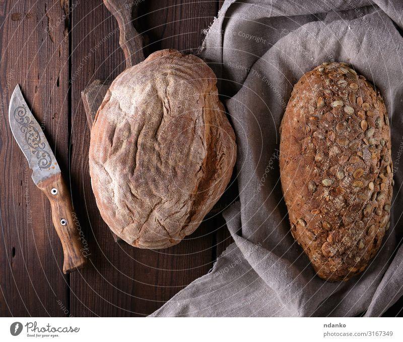 Brot aus Roggenmehl mit Kürbiskernen Ernährung Frühstück Diät Tisch Holz frisch natürlich oben braun grau Tradition Messer Feinschmecker Mehl backen Bäckerei