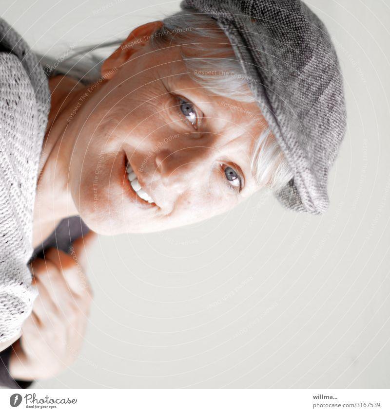 Porträt einer lächelnden grauhaarigen Frau mit Schiebermütze blond Schirmmütze Ganovenmütze Lächeln lachen Freundlichkeit Lifestyle lässig Erwachsene