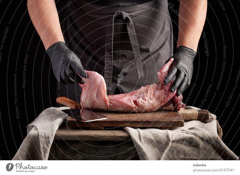 der Koch in schwarzen Latexhandschuhen hält einen ganzen Kaninchenkadaver Fleisch Ernährung Abendessen Messer Tisch Küche Mann Erwachsene Hand Handschuhe Holz