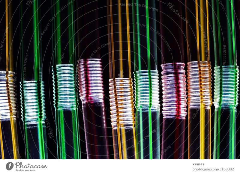 Trinkhalme aus Plastik vor schwarzem Hintergrund Röhren Kunststoff Einweg dunkel lang gelb grün rot Umweltverschmutzung durchsichtig Kunststoffmüll