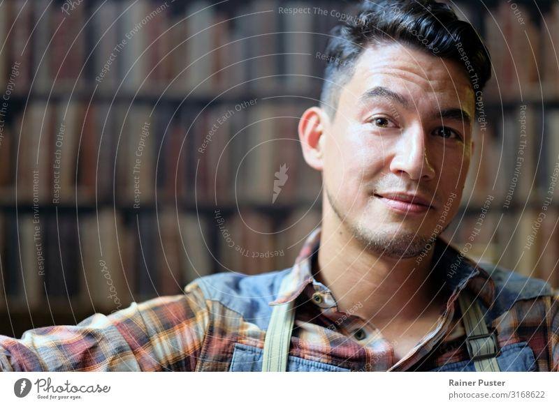 Portrait vor Bücherwand maskulin Mann Erwachsene Gesicht 1 Mensch 30-45 Jahre Buch Bibliothek Hemd Hosenträger schwarzhaarig Coolness Freundlichkeit mehrfarbig