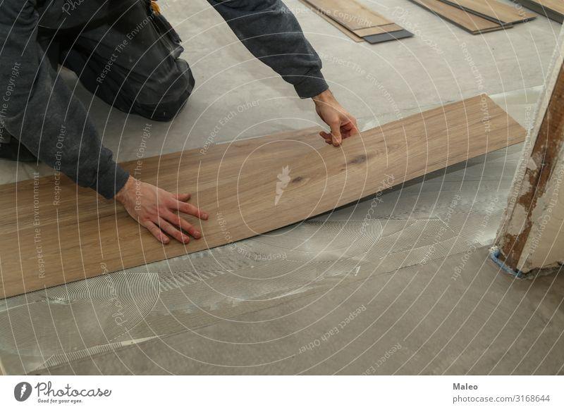 Ein Arbeiter installiert neuen Vinylfliesenboden Mann Baustelle Reparatur Haus Wohnung Bodenbelag Fliesen u. Kacheln Installationen Material Schallplatte