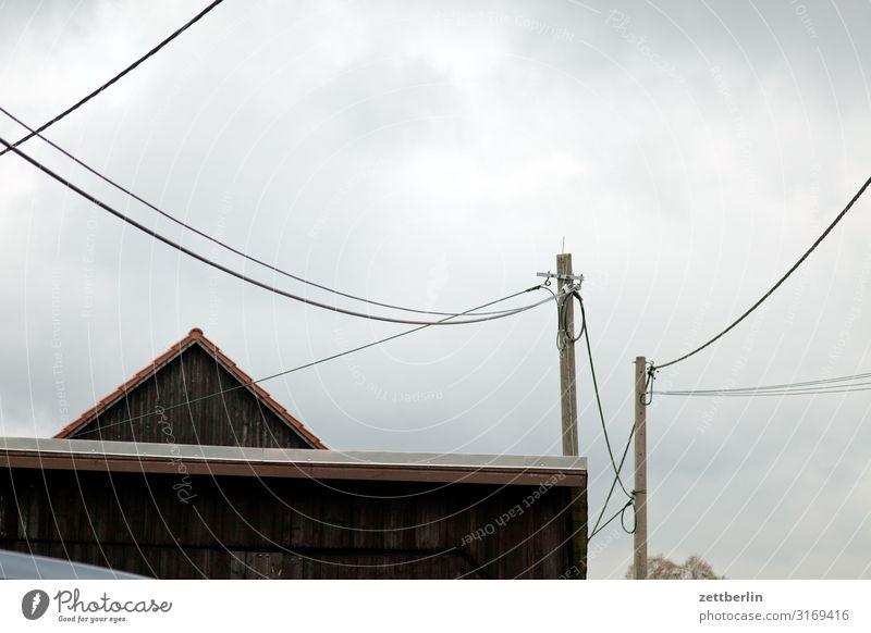 Dorf mit Kabeln Berge u. Gebirge Haus Scheune Dachgiebel Mast Strommast Telefonmast Telefonleitung Leitung link Verbindung Telekommunikation Himmel