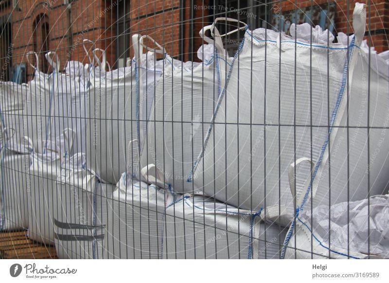 große gefüllte weiße Kunsstoffsäcke stehen aufeinander hinter einem Bauzaun Hamburg Hafenstadt Mauer Wand Sack Zaun Stein Metall Kunststoff Linie festhalten