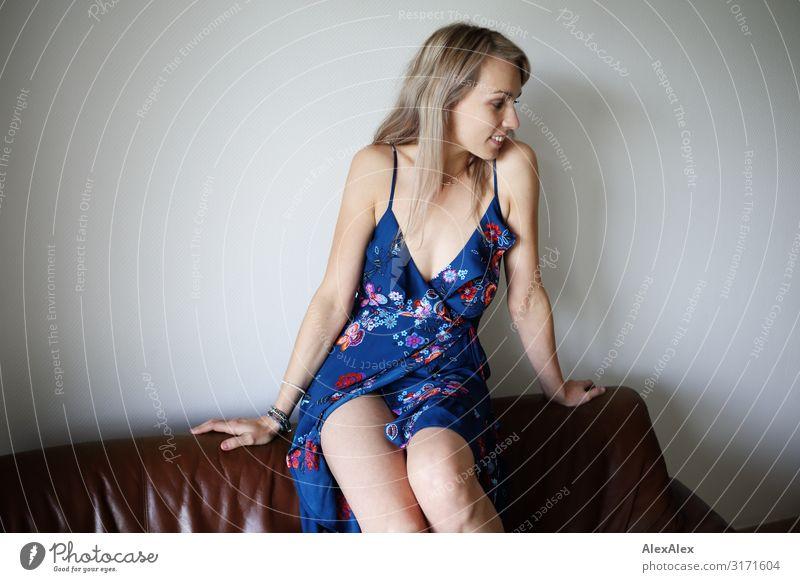 Frau sitzt auf Rückenlehne der Couch blau Stadt schön Freude Erwachsene natürlich feminin Glück Stil Häusliches Leben blond Lächeln sitzen ästhetisch