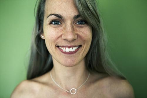 Portrait einer Frau vor grüner Wand Stil Freude schön Leben harmonisch Erwachsene Sommersprossen 30-45 Jahre Schmuck blond langhaarig Lächeln Blick ästhetisch