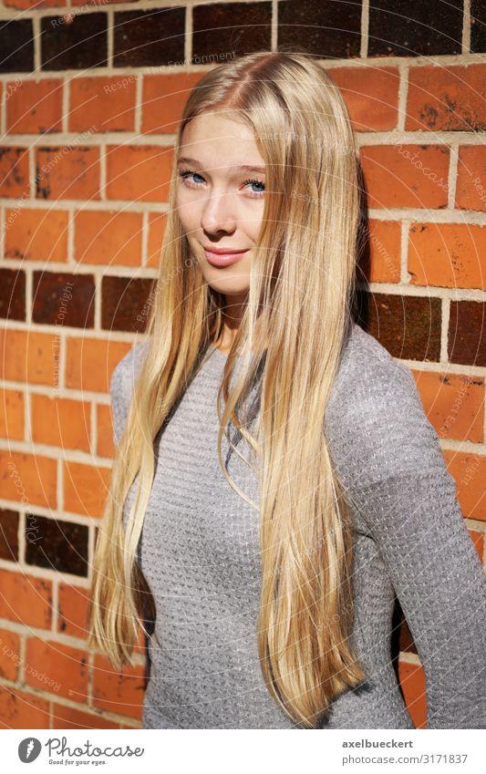 weiblicher Teenager lehnt an Mauer Lifestyle Mensch feminin Junge Frau Jugendliche Erwachsene 1 13-18 Jahre 18-30 Jahre Wand Pullover blond langhaarig Lächeln