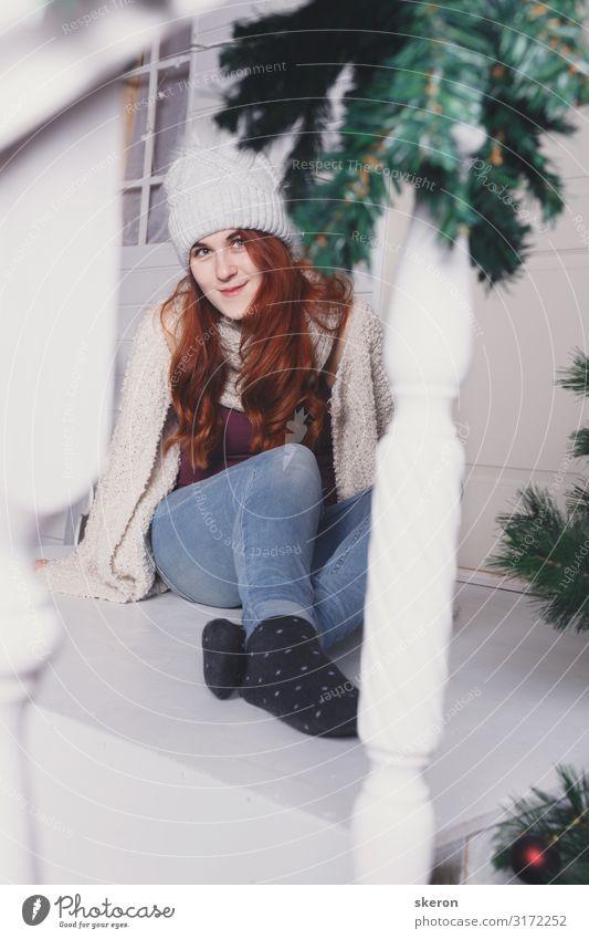 Mädchen mit Winterhut sitzt auf der Veranda eines Weihnachtshauses Lifestyle kaufen Freizeit & Hobby Entertainment Party Veranstaltung Weihnachten & Advent