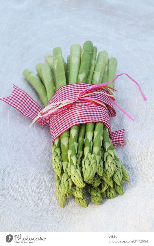 Eine Portion grüner Spargel, frisch geerntet vom einheimischen Feld, liegt dekoriert mit einem kariertem Band aus Stoff, zusammen gebunden, im Licht auf dem Tisch, mit einem weißem Tuch aus Leinen.