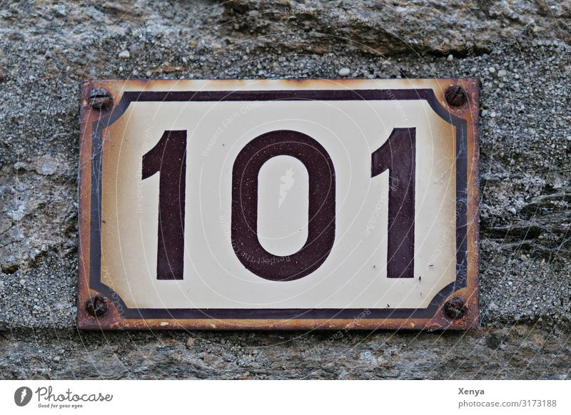 Schild 101 Mauer Wand Fassade Stein Metall braun grau weiß Hausnummer Ziffern & Zahlen Rost Blechschild alt Gedeckte Farben Außenaufnahme Menschenleer Tag