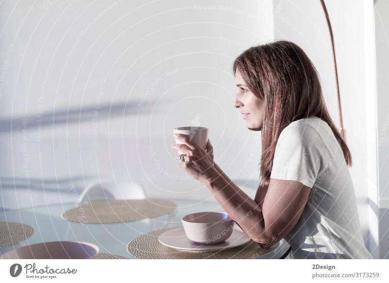 Frau, die auf dem Wohnzimmer sitzt und eine Tasse Tee hält. Frühstück Getränk trinken Heißgetränk Kaffee Lifestyle Glück schön Erholung Freizeit & Hobby Haus