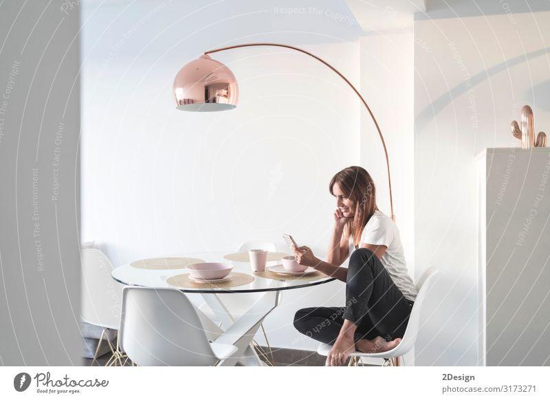 Erwachsene Frau, die im Wohnzimmer sitzt, während sie telefoniert. Lifestyle Glück schön Erholung Wohnung Haus Schreibtisch Sofa Tisch Telefon Handy PDA