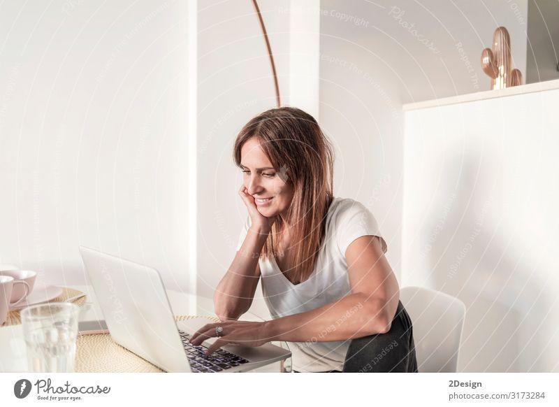 Erwachsene Frau, die zu Hause mit dem Laptop arbeitet. Lifestyle kaufen Glück schön lesen Lampe Schreibtisch Tisch Wohnzimmer Erfolg Arbeit & Erwerbstätigkeit
