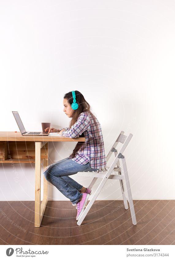 Bildung. Hausunterricht, junge Teenager lernen am Laptop, hören Musik mit Kopfhörern, sehen sich online ein Video an, machen Wissenschaft und Biologie. Elearning-Konzept