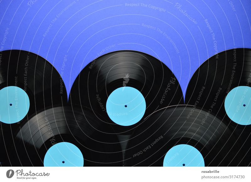 fünf alte schwarze Vinyl Schallplatten aufeinander gelegt mit leerem türkis farbenem Label auf blauem Hintergrund als Band unten mit Freiraum für Text oben| Symmetrie