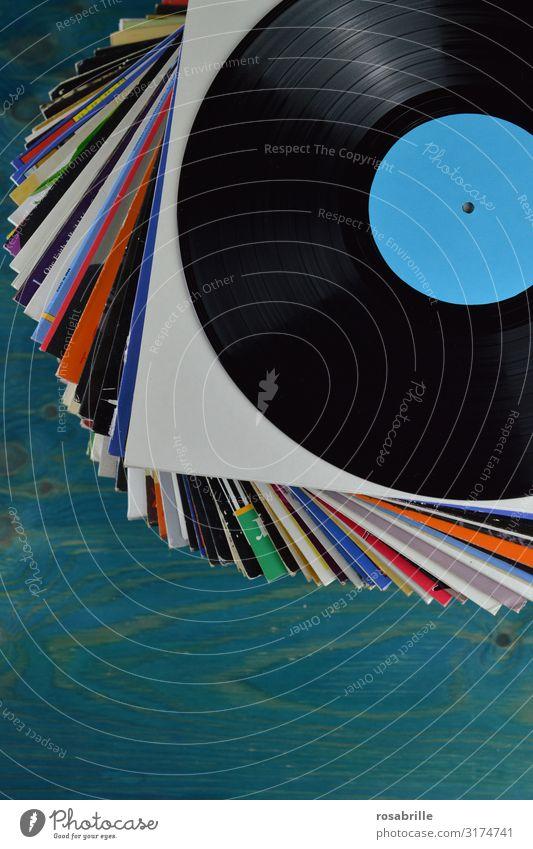 Stapel mit vielen alten Vinyl Schallplattenhüllen aufeinander mit einer schwarzen Schallplatte oben drauf mit neutralem türkis farbenem Label auf blauem Holztisch | alt