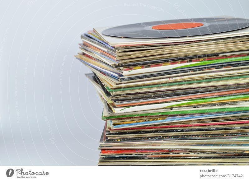 Stapel mit vielen alten bunten Vinyl Schallplattenhüllen aufeinander mit einer schwarzen Schallplatte oben drauf mit neutralem orangenem Label vor weißem Hintergrund mit Freifläche für Text links | alt