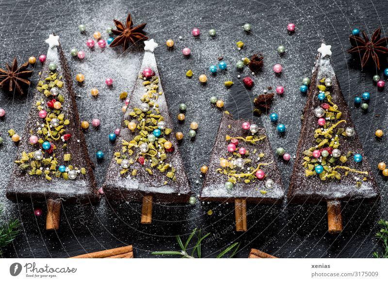 vier weihnachtlich dekorierte Tannenbäume aus Schokoladenkuchen mit Zuckerperlen, Sternanis und Zimtstangen Kuchen Weihnachten & Advent Tannenbaum Lebensmittel