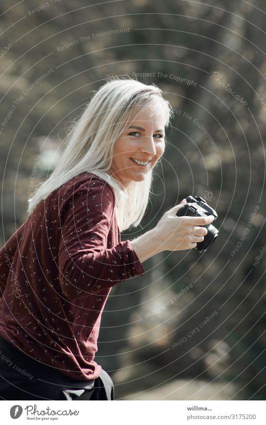 junge blonde fotografin mit schelmischem lächeln Junge Frau Fotograf langhaarig lachen Freundlichkeit Fotokamera Lächeln lustig Fröhlichkeit Verschmitzt Humor
