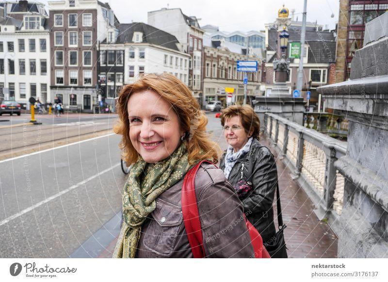 Zwei Frauen mittleren Alters, die auf der Brücke in Amsterdam stehen. Lifestyle Ferien & Urlaub & Reisen Tourismus Erwachsene Wolken Stadtzentrum Straße Lächeln