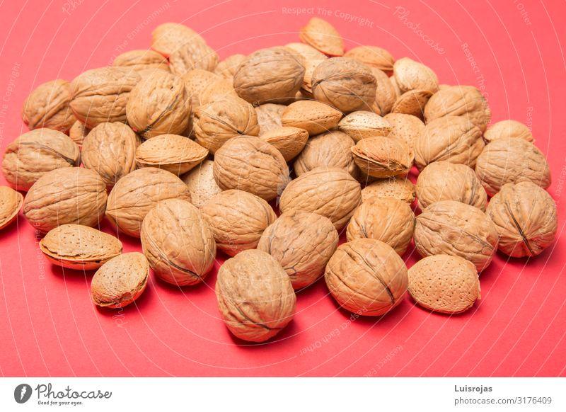 Nüsse und Mandeln auf rotem Hintergrund Lebensmittel Nuss Picknick Bioprodukte Vegetarische Ernährung Diät Design Herbst Wärme braun gelb Trockenfrüchte