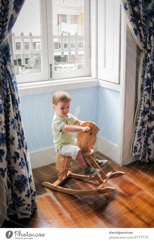 Kleiner Junge reitet auf einem alten Schaukelpferd Freude Spielen Kind Baby Kleinkind Kindheit Pferd Spielzeug Holz sitzen niedlich retro braun Kaukasier