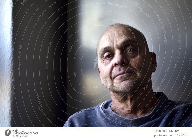 Ganz natürliches Frontal Portrait eines reifen Mannes mit Beinahe-Glatze, der von weichem, seitlichem Tageslicht beleuchtet leicht von oben, ernst, tiefgründig und furchtlos direkt in die Kamera blickt