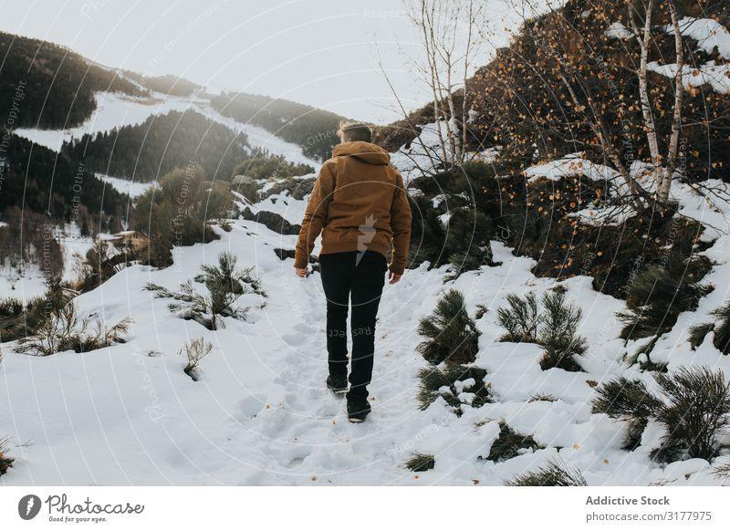 Mann, der auf einem Wanderweg in einer verschneiten Landschaft geht. laufen Schnee Fußweg Berge u. Gebirge Berghang Natur Aktion Wanderer Tag Bewegung Winter