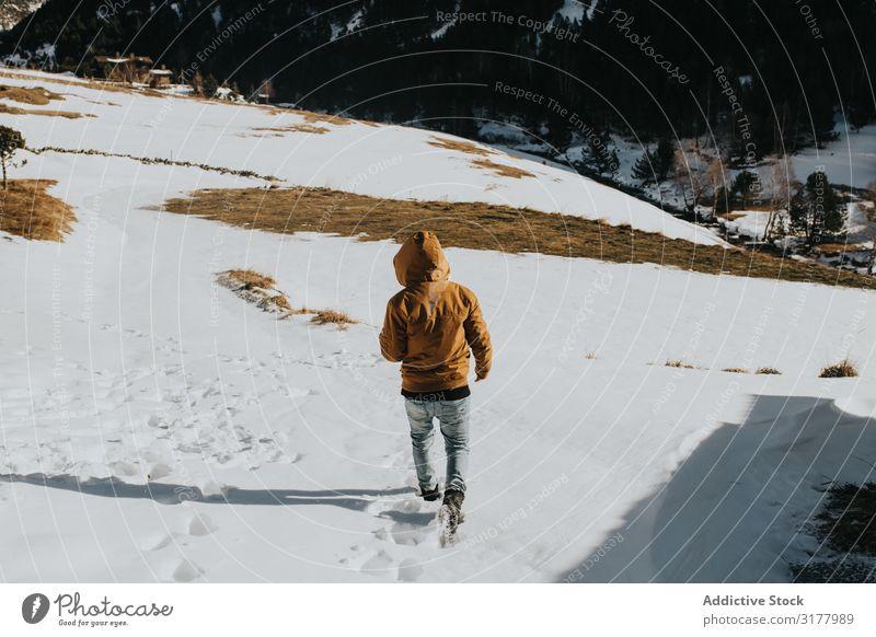 Mann, der auf einem Wanderweg in einer verschneiten Landschaft geht. laufen Motorhaube Schnee Fußweg Berge u. Gebirge Berghang Natur Aktion Wanderer Tag