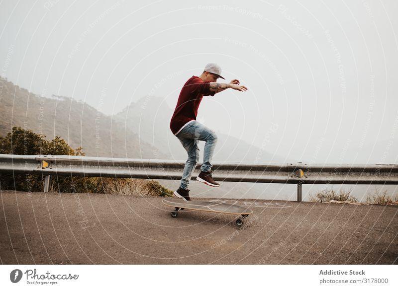 Trendige Skateboarderin mit Tricks in der Natur Mann Berge u. Gebirge Straße Ausritt Longboard springen Nebel Landschaft abgelegen Panorama (Bildformat)