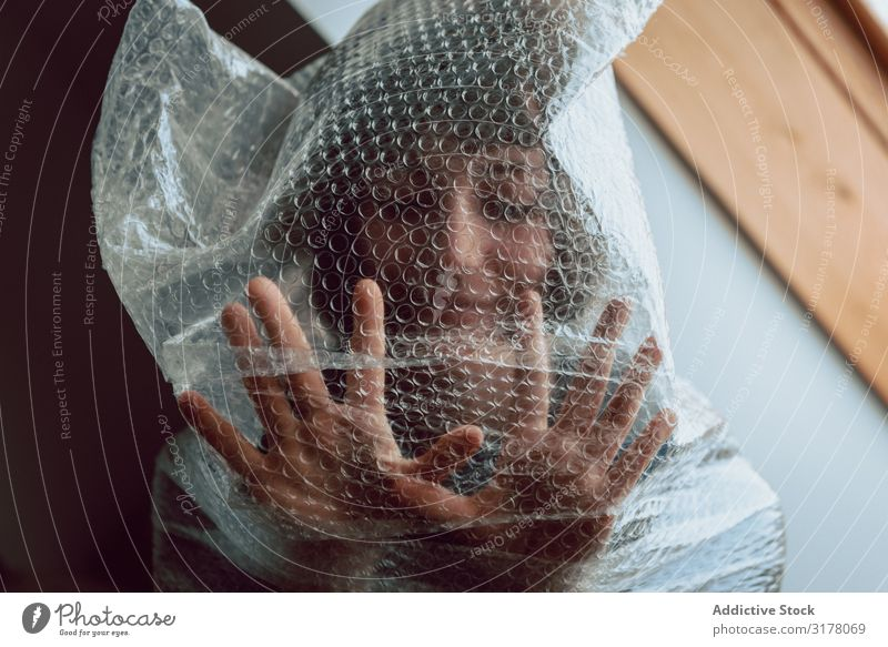 Frau in Luftpolsterfolie verstrickt Kunststoff reduzieren Zerstörung Müll Müllbehälter