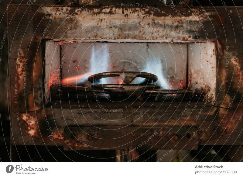 Hufeisenschmelzen im Ofen Metall Verhüttung Schmelzofen Fälschung Hufschmied Werkstatt Ranch Industrie heiß Eisen Flamme Feuer Produktion geschmolzen Gerät