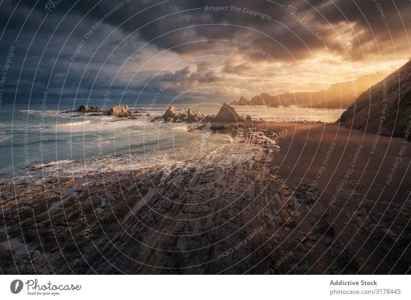 Malerischer Küstenstreifen mit Felsen bei strahlendem Sonnenuntergang Seeküste malerisch hell Strand Wolken Regen Stein winken Landschaft Aussicht Natur schön