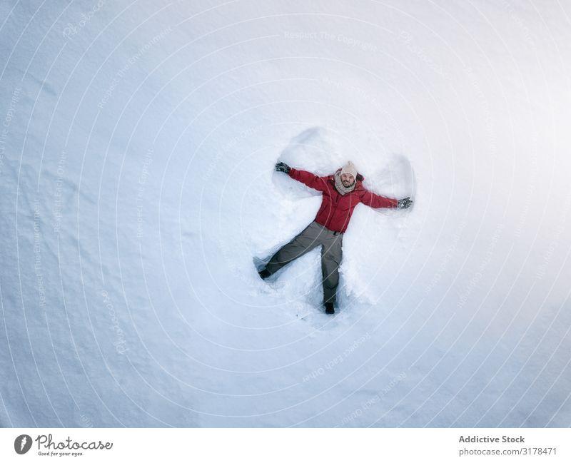 Lächelnder Mann, der auf frischem, sauberen Schnee liegt. Engel spielerisch Natur Ferien & Urlaub & Reisen Freude Vergnügen lügen Lebensmitte lustig Silhouette