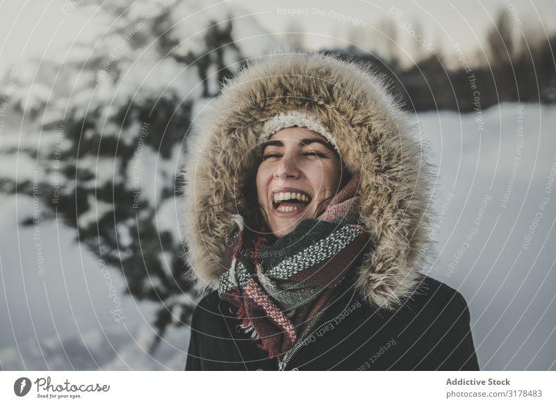 Junge Frau lacht auf verschneitem Hintergrund lachen Freude Schnee attraktiv Jugendliche Wärme Bekleidung Pelzmantel Baum Konifere Winter Glück Fröhlichkeit