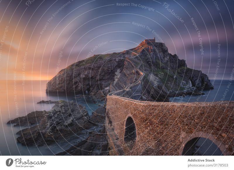 Einsame felsige Insel mit Kapelle und Steinbrücke Felsen Sonnenuntergang san juan gaztelugatxe Spanien Brücke Natur Küste Landschaft Langzeitbelichtung Wasser