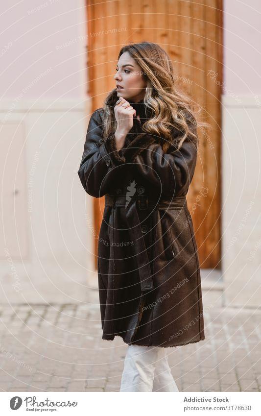 Stilvolle Frau, die neben der braunen Tür steht. Haus stehen Efeu Straße heimwärts Hauseingang Glück Freude Außenseite modern Lifestyle Freizeit & Hobby Dame