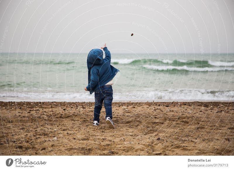 Kind wirft einen Stein ins Meer Leben Spielen Strand Wellen Winter Mensch maskulin Kindheit Körper 1 1-3 Jahre Kleinkind Herbst Jeanshose Sand blau Lebensfreude
