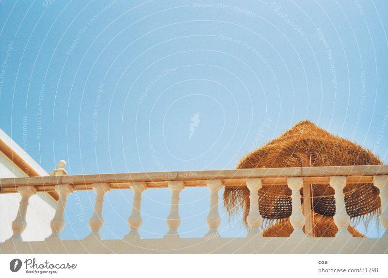 Sonnendeck Balkon Sommer Ibiza Stroh Sonnenschirm Sonnendach Physik Architektur Geländer Himmel blau Wärme