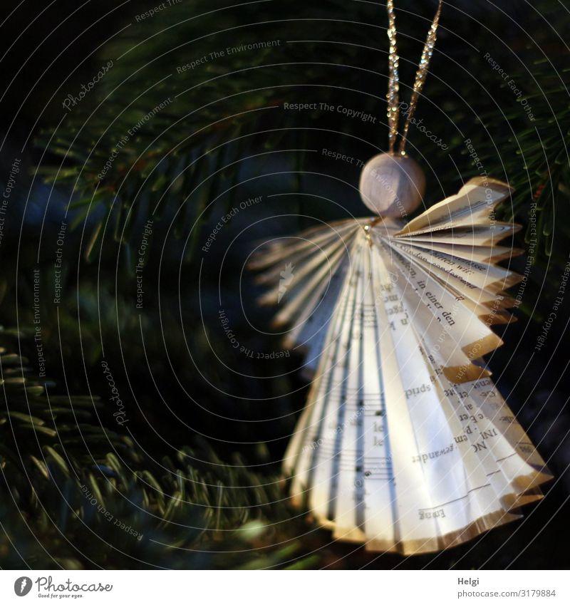 gebastelter Engel aus Notenpapier mit einer Holzkugel als Kopf hängt als Dekoration an einem Tannenbaum Feste & Feiern Weihnachten & Advent
